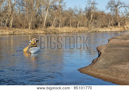 senior paddler in a decked expedition canoe on the South Platte River in eastern Colorado, winter scenery without snow