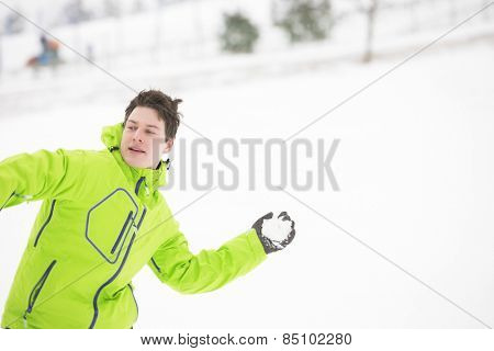 Young man in hooded jacket throwing snowball