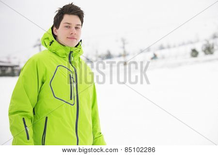 Portrait of young man wearing hooded jacket in snow