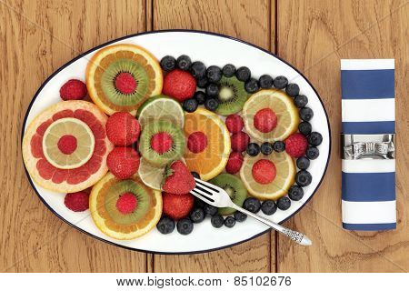 Fruit selection for antioxidant  health food diet on an oval plate with old silver fork and napkin with ring over oak background.