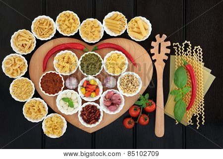 Italian pasta and mediterranean food ingredients on a heart shaped board in porcelain bowls over dark wood background.
