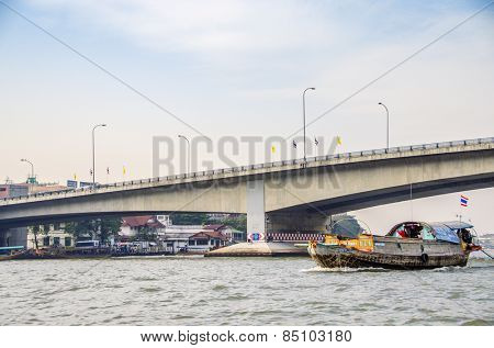 BANGKOK, THAILAND, DECEMBER 26, 2012: A boat pass below the bridge on Chao Praya River