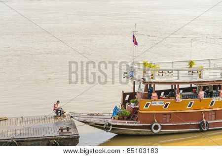 PHNOM PENH, CAMBODIA, JANUARY 2, 2013: Local man seats near the boat on pier in International port waiting for tourists