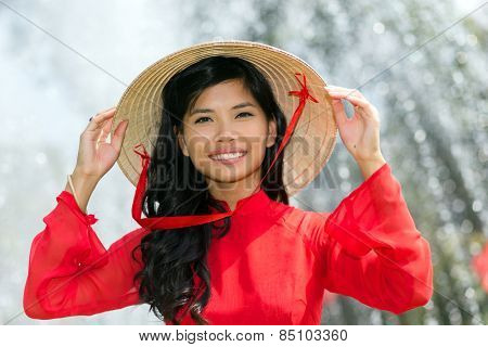 Smiling vivacious Vietnamese woman in a traditional red outfit and conical hat standing in front of a fountain smiling at the camera