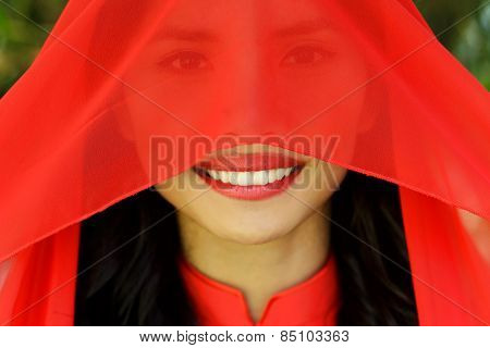 Close up Happy Young Asian Woman with Red Scarf Covering her Face, Looking at the Camera with a Smile