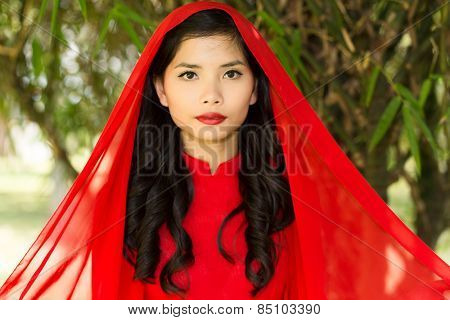 Close up Young Pretty Asian Woman in Red Dress with Head Scarf with Long Wavy hair Looking at the Camera.