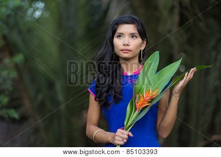 Half Body Shot of a Young Pretty Vietnamese Woman in Blue Ao Dai Dress Holding Orange Flowers with Big Leaves, Looking Up.