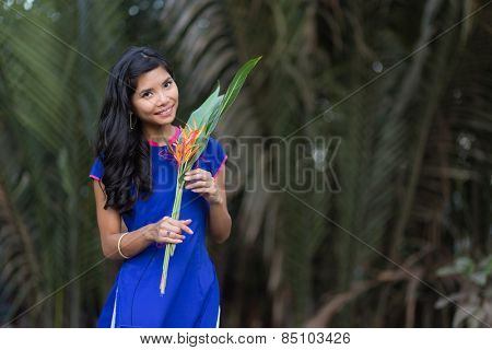 Smiling Young Vietnamese Woman in Blue Dress Holding Fresh Flowers with Big Green Leaves While Looking at the Camera.