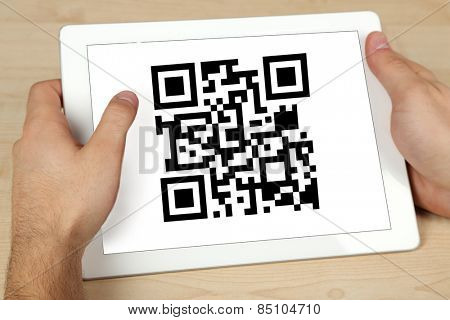Hand holding tablet with QR code on screen