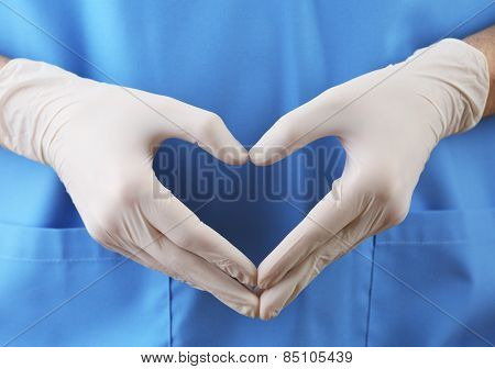 Doctor showing shape of heart by his hands in sterile gloves, closeup view