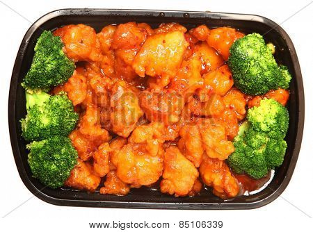 To go or delivery container of general tso chicken and broccoli. Top view over white.