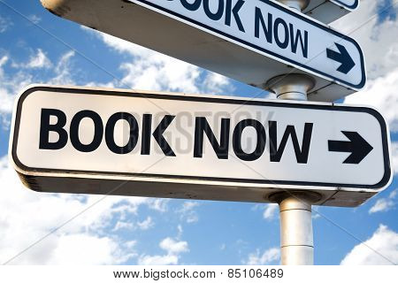 Book Now direction sign on sky background