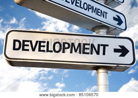 Development direction sign on sky background
