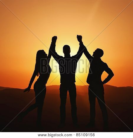 Group Of People At Sunset Rejoices Victory