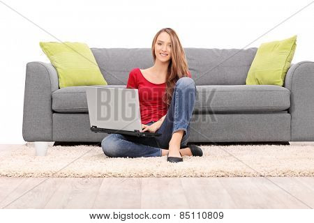 Young woman working on laptop seated on the floor isolated on white background