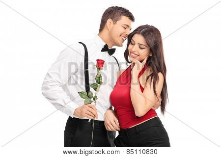 Romantic guy whispering something to a girl and holding a red rose isolated on white background
