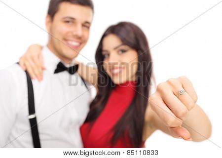 Woman posing with her fianc���©e and showing her engagement ring with the focus on the ring isolated on white background