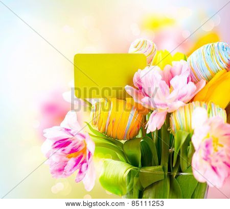Easter Holiday flowers bunch with greeting card. Colorful tulips flowers bouquet decorated with colourful eggs and invitation blank card. Easter art design. Springtime