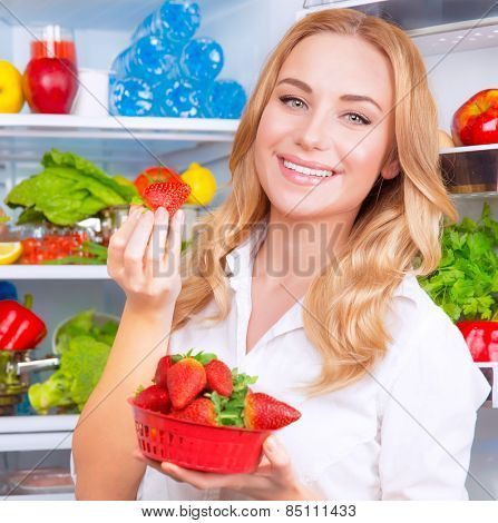 Closeup portrait of beautiful female eating strawberry, open fridge full of fruits and vegetables, dieting and healthy eating concept