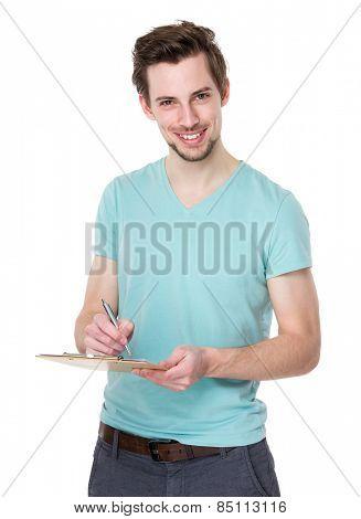 Caucasian man write on clipboard