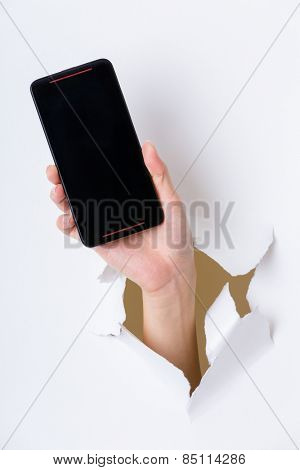 Hand holding mobile phone bursting through paper