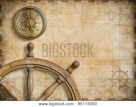 steering wheel and compass with vintage nautical map