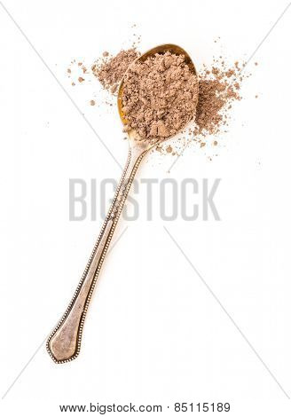 ground cinnamon powder in a spoon on a white background
