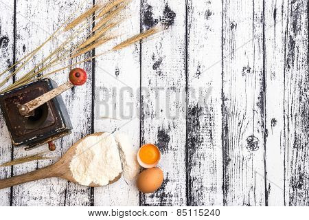 flour, eggs and wheat ears on a textured wooden table and wheat ears on a textured wooden table