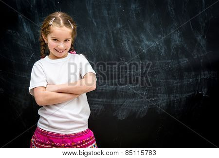 cute little girl smiling with arms folded against the black school board