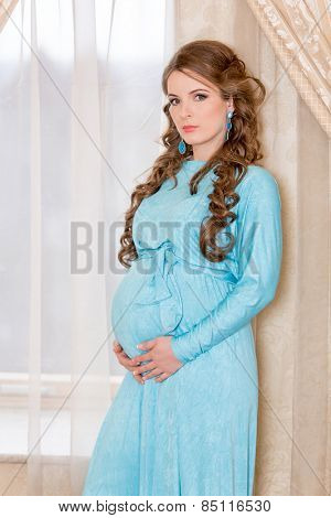 Beautiful pregnant woman in white shirt. Expectant mother.