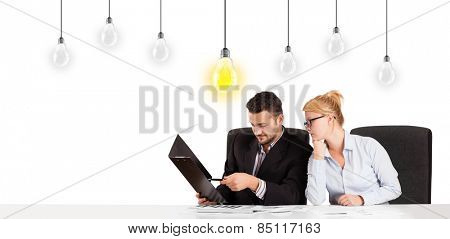 Business man and woman sitting at table with bright idea light bulbs