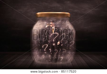 Businessman locked into a jar with question marks concept on background