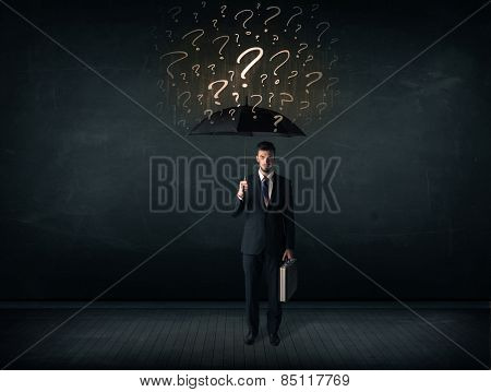 Businessman with umbrella and a lot of drawn question marks concept on background