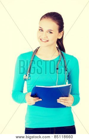 Beautiful happy medicine student with note pad.