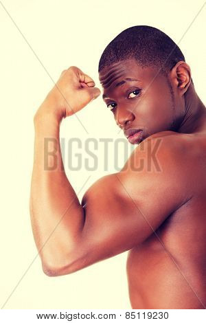 Casual young african muscular man showing his biceps.