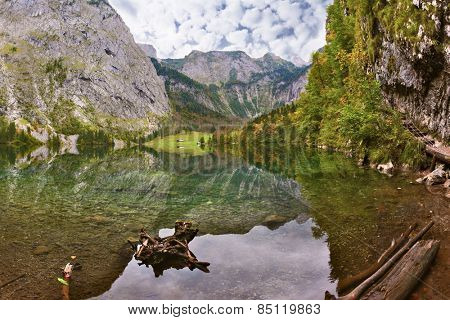Magic reflection in German lake Koenigssee. Clouds and mountains reflected in the mirrored surface of the water. Cloudy day on the lake