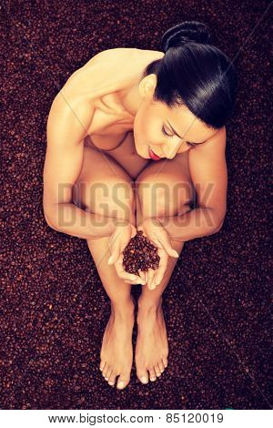 Beautiful undressed woman sitting in coffee beans.