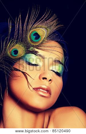 Beauty woman with artistic make up and peacock feather.