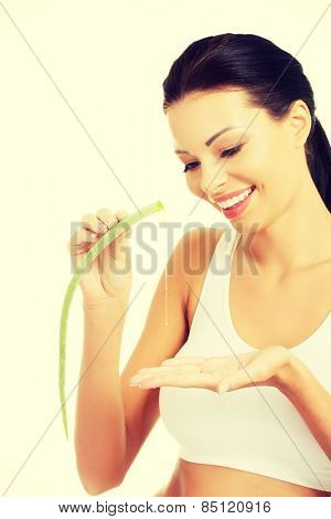Beautiful spa woman squeezing juice from aloe vera.
