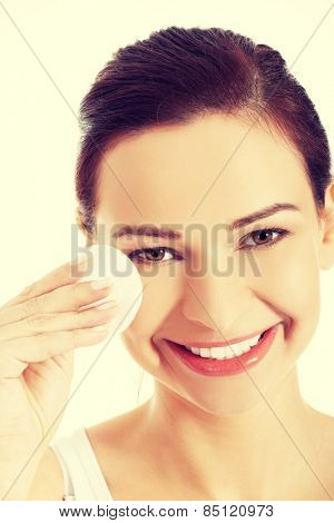 Beautiful woman removing face makeup with cotton pad.