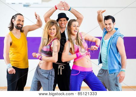 Group of men and women dancing fitness choreography in dance school
