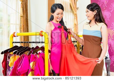 Asian young sales lady offering dress to woman in fashion store