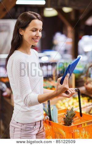 sale, shopping, consumerism and people concept - happy young woman with food basket and tablet pc computer in market