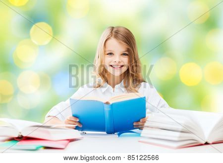 education, people, children and school concept - happy student girl reading book at school over green lights background