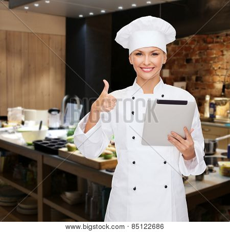 cooking, bakery, people, technology and food concept - smiling female chef cook or baker with tablet pc computer showing thumbs up over restaurant kitchen background
