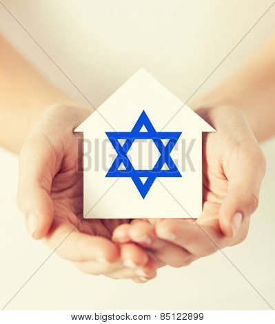 religion, judaism and charity concept - female hands holding paper house with star of david symbol