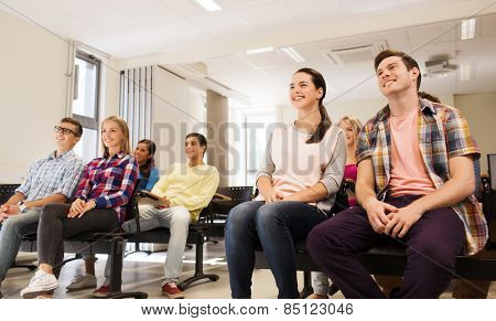 education, high school, teamwork and people concept - group of smiling students sitting in lecture hall