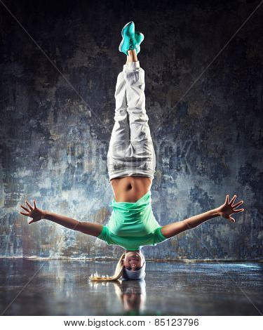 Young woman hip-hop dancer standing on head on wall background.