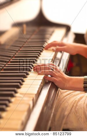 Young woman playing piano. Hands close-up view.