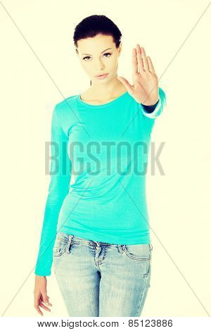 Young caucasian woman making stop sign with her hand.